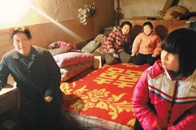 图为老人和三个孩子生活条件很简陋却充满温情。