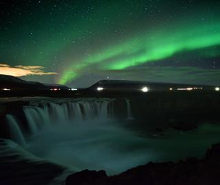 冰岛瀑布上空出现璀璨极光