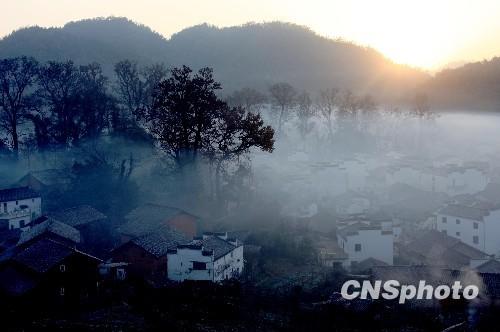 2010年1月14日晨,雨后转晴,江西婺源石城出现烟雾缭绕的美景,如同天宫浮云,海市蜃楼,一幢幢徽派古民居时隐时现,宛如仙境一般,如临神奇幻境。中新社发 方也广德 摄