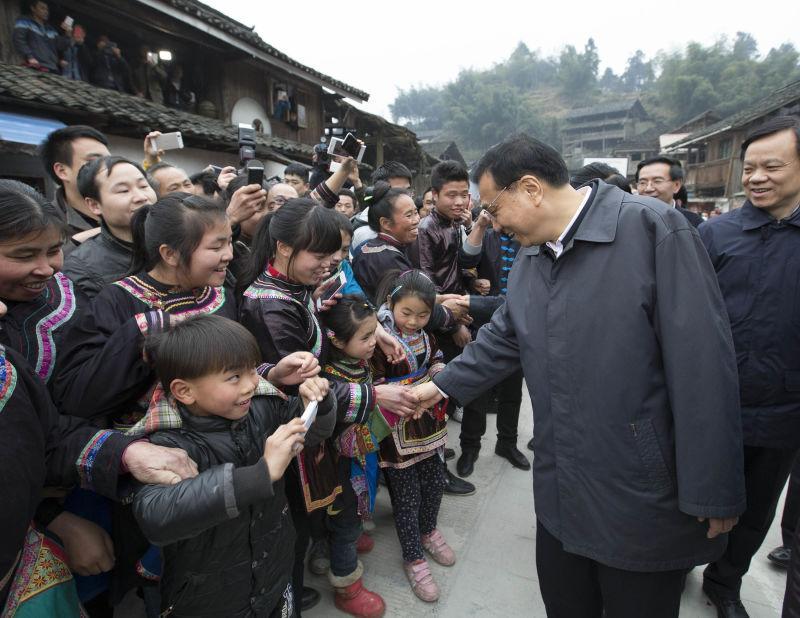 """这个留着西瓜头的小男孩最终吸引了李克强的注意。总理停下脚步,笑着拉着他的手问道:""""手机是谁给你的?"""""""