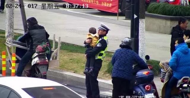 交警抱娃指挥交通 网友质疑:怎么执勤