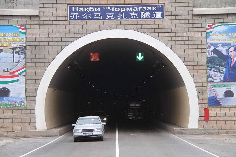 """这是2013年11月6日,车辆从通往塔吉克斯坦首都杜尚别的塔中公路乔尔马克扎克隧道通过。在塔吉克斯坦交通""""大动脉""""上,随处都能看见中国路桥等企业留下的印记。新华社记者 沙达提 摄"""