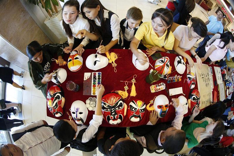 """这是2016年9月27日,在吉尔吉斯斯坦首都比什凯克,学生在吉尔吉斯国立民族大学孔子学院举办的""""孔子学院日""""的文化体验区学习绘制京剧脸谱。新华社发(罗曼摄)"""